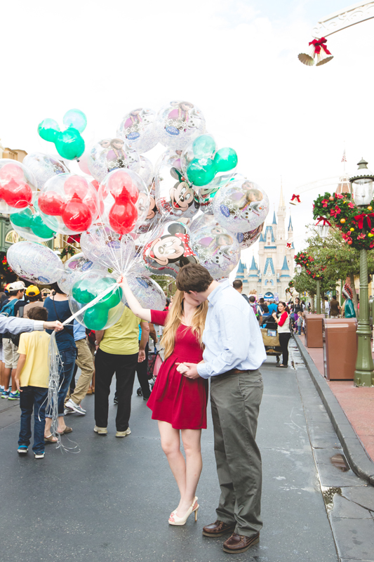 Disney Magic Kingdom Engagement photos couple holding Disney balloons on main street