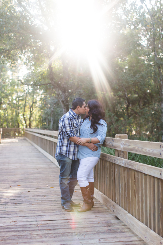 Downtown Celebration Engagement Session Photos - Couple kissing on boardwalk with sunflare