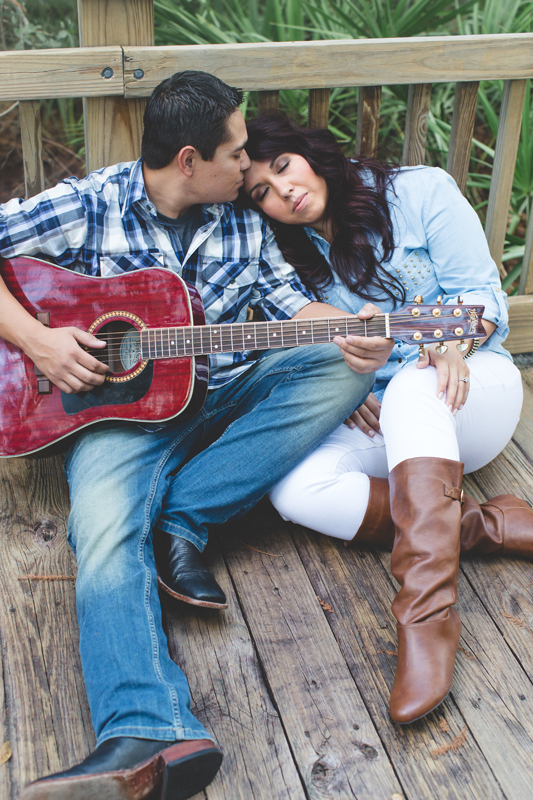 Downtown Celebration Engagement Session Photos - couple with guitar sitting pose