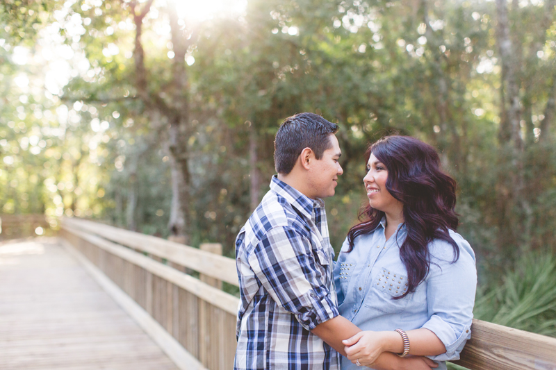 Downtown Celebration Engagement Session Photos - Couple embracing with trees behind them