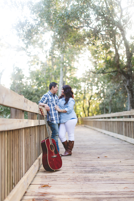 Downtown Celebration Engagement Session Photos - Couple posing with guitar hugging