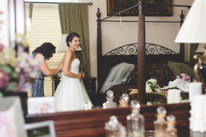 intimate wedding in a house - bride getting into her dress