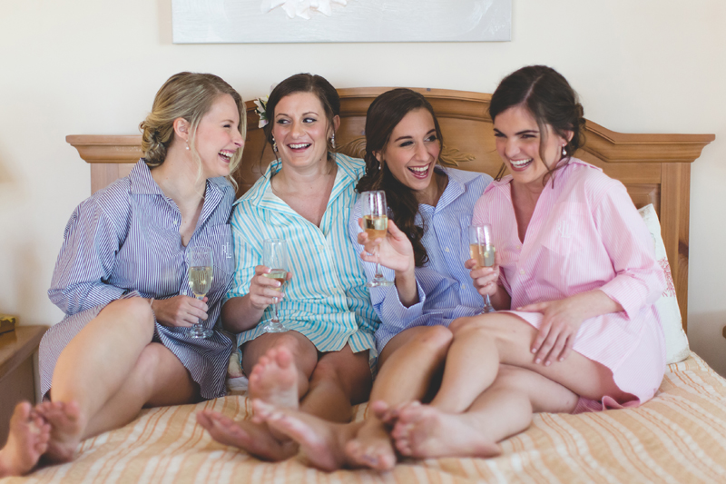 Bride and wedding party sitting on bed drinking champagne - Beach Wedding Photos - destination Orlando wedding photographer - Jaime DiOrio