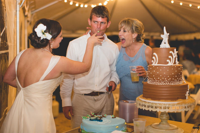 Bride shoving cake in Grooms face - Beach Wedding Photos - destination Orlando wedding photographer - Jaime DiOrio