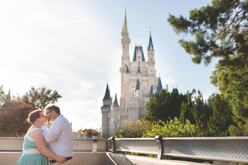 Couple kissing in front of Disney castle - Magic Kingdom photo shoot-Disney family session - family photos - Jaime DiOrio Disney Photographer