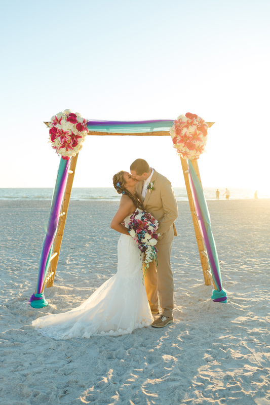 Bride and Groom kissing under bamboo arch - Tradewinds Island Grand Resort beach wedding - st pete beach - Jaime DiOrio Photography - Destination Orlando wedding photographer -  (53).JPG