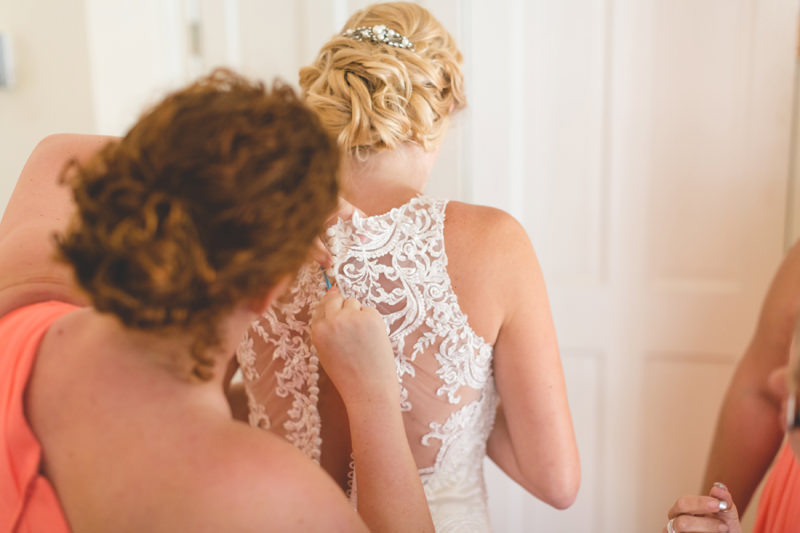 Bridesmaids buttoning Bride into gorgeous lace wedding dress