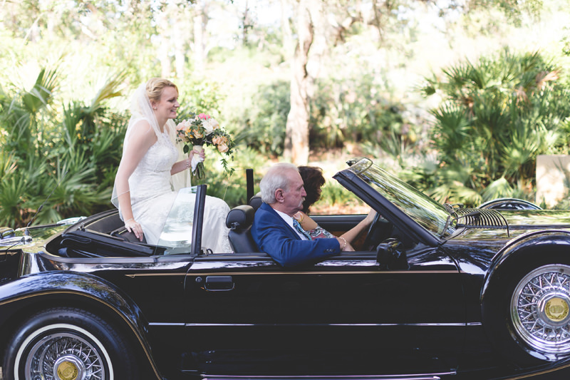 Bride rides on a vintage car to her outdoor spring ceremony
