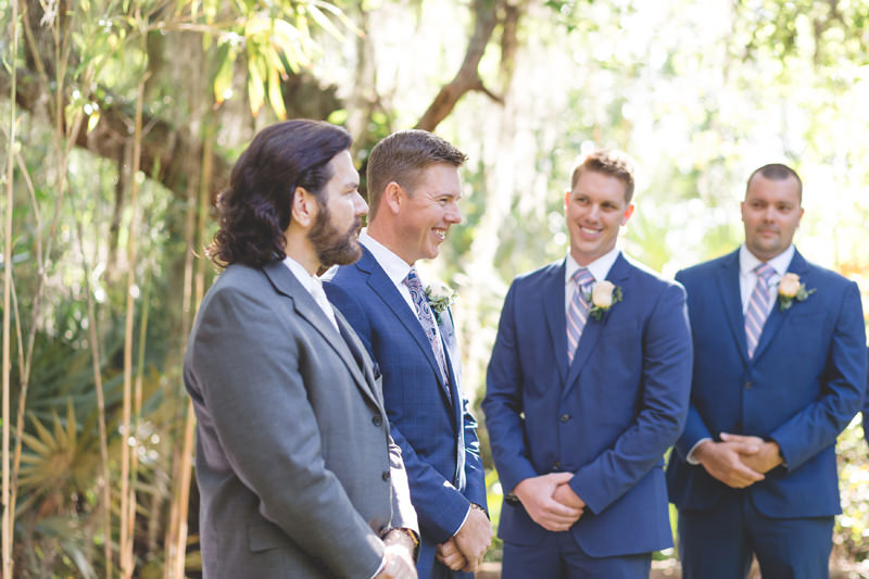 Groom smiling with groomsmen at ceremony waiting for Bride