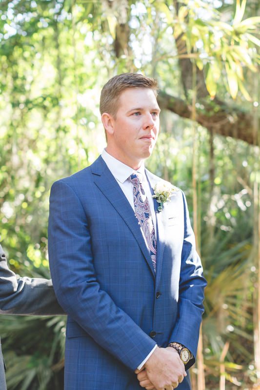Groom sees Bride walking down aisle at outdoor ceremony