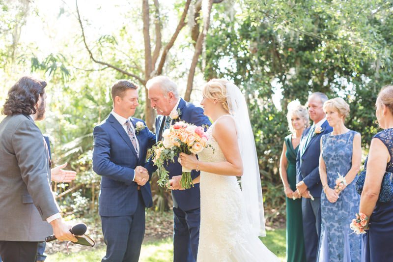 Groom shaking the hand of the Father of the Bride at an outdoor ceremony