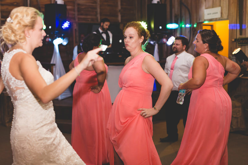 Bride dancing with bridesmaids in coral dresses at spring wedding reception