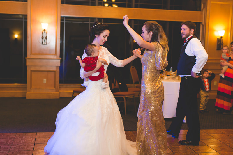 Bride dancing with bridesmaid in gold sequins dress