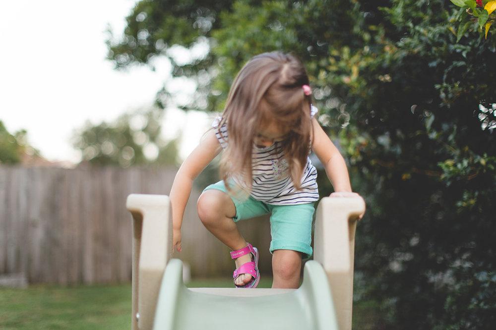 little girl climbing up slide photo - orlando documentary family photographer - Jaime DiOrio.jpg