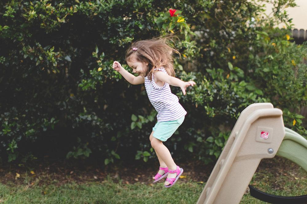 little girl jumping from slide photo - orlando documentary family photographer - Jaime DiOrio.jpg