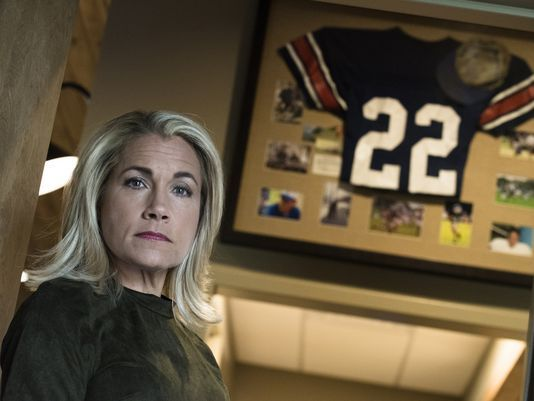 Rebecca Ellis standing in front of a framed jersey and photos of her son Cole.