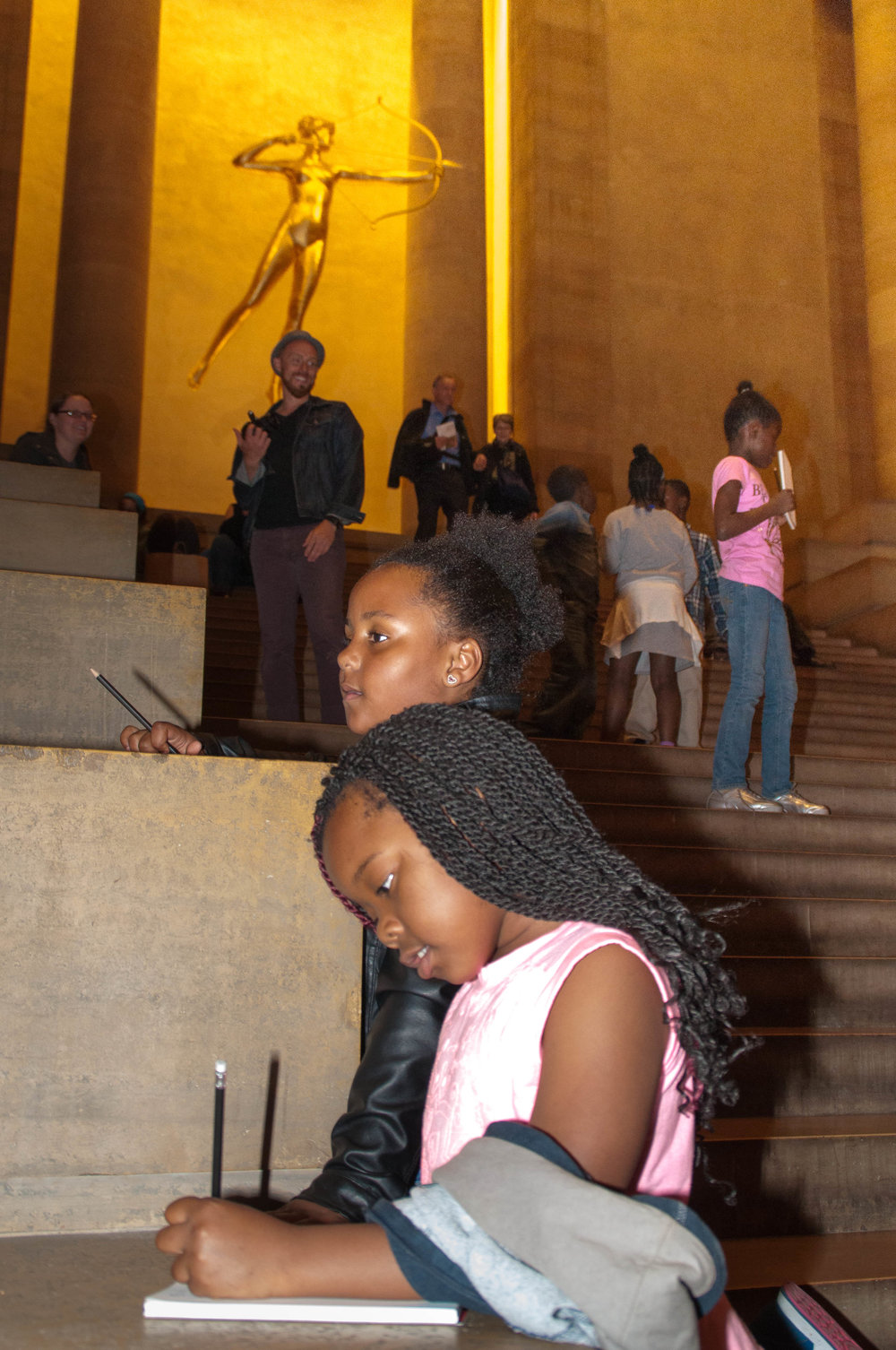 Two young visitors write poems on the Great Stair. Photo by Tieshka Smith.