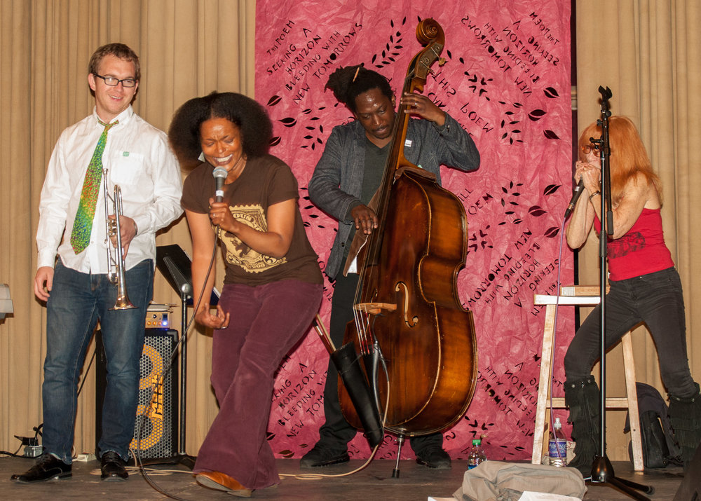 Yolanda Wisher and The Afroeaters perform at City of Poetry in front of a Karina Puente hand-cut backdrop. Photo by Tieshka Smith.