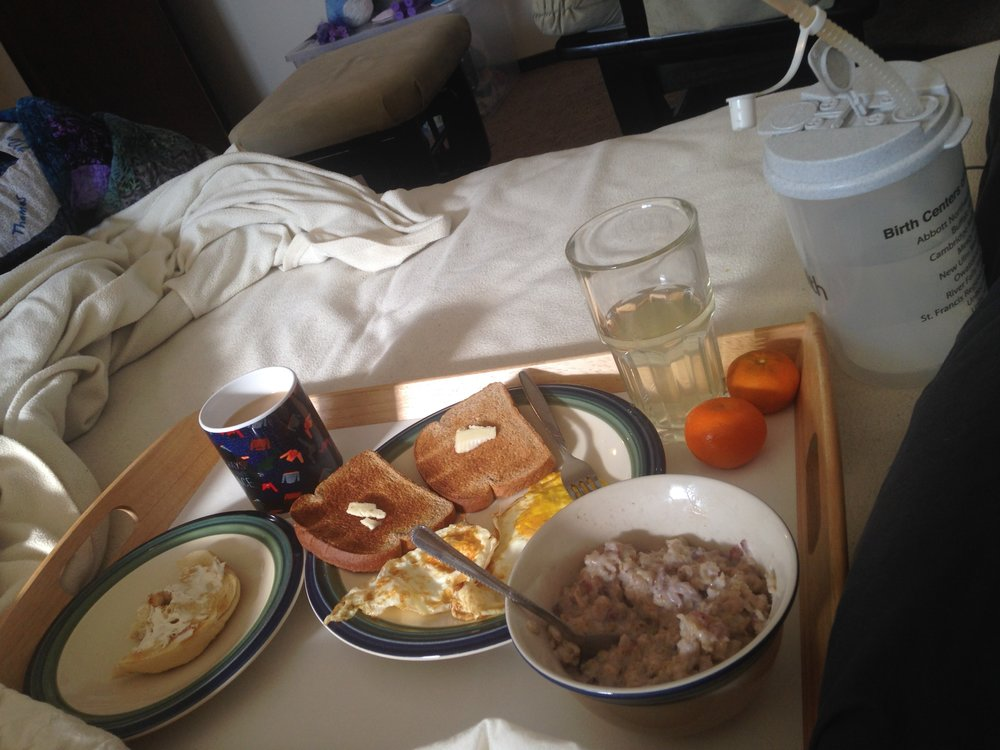 An example of a postpartum breakfast delivered to me by my fabulous birth team, so I was able to stay in bed and be with baby. Yes, I realize that's a lot of food, and yes I did eat it all because  breastfeeding . (Image: A serving tray holding a plate with a half-eaten bagel, another plate with two pieces of toast and two eggs, two tangerines, a cup of coffee, a large bowl of oatmeal with fruit, a glass of electrolyte drink, and a large bottle of water with a straw).