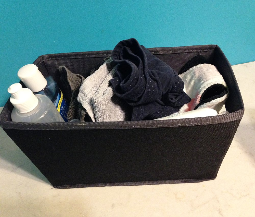This is a picture of my postpartum basket, which I had easily on hand and my care team would restock for me in the bathroom. Some of what saved me constant trips to and from my closet were, ample postpartum pads, clean underwear, and cloth wipes for the sore perineum. (Image: Black basket with two bottles on the left and a variety of cloths, pads, and underwear inside).