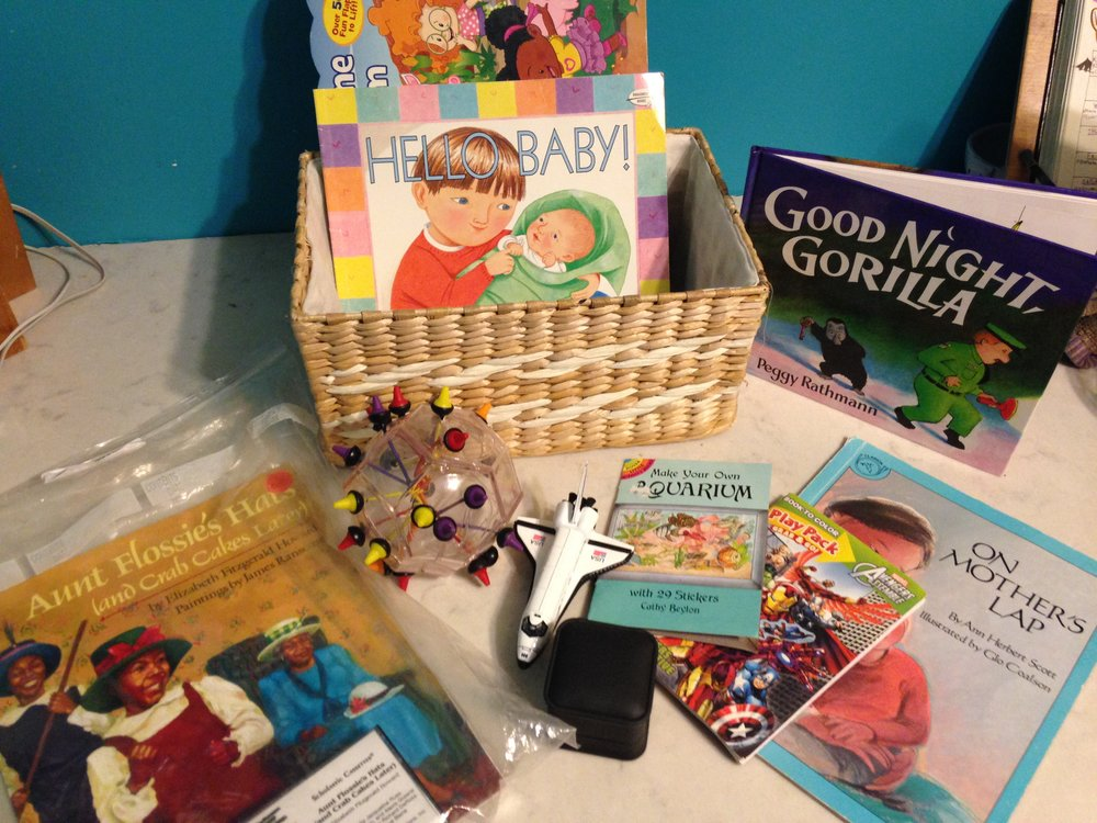 A sibling prep basket with books, stickers, and toys. More details to be included on next weeks blog post! Image (A woven basket with the book Hello Baby in it. On the counter in front of it are a variety of toys, books, and sticker books).