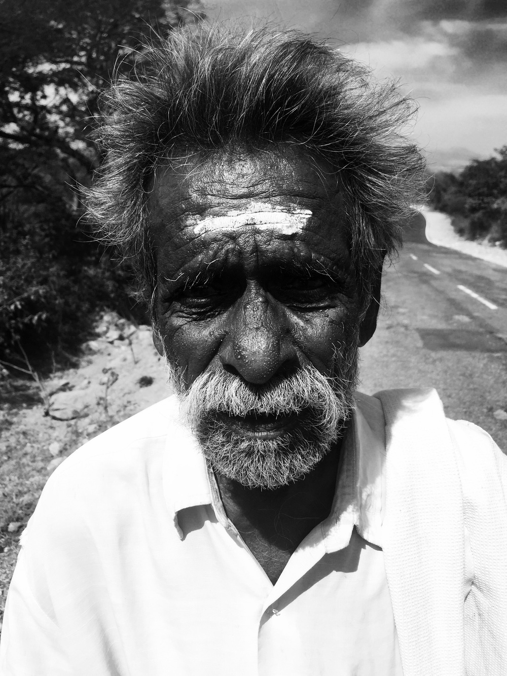 A man walking on the side of the road, barefoot. I wonder how far they've walked in the day?
