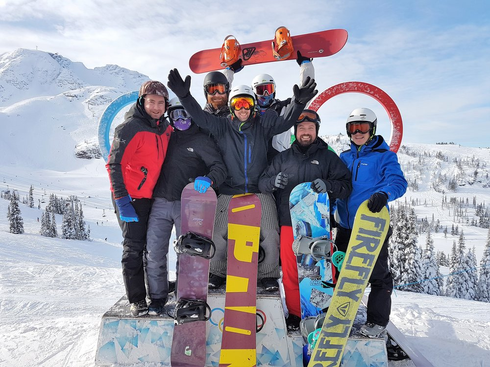 Group photo of snowboarders infront of the logo of the Olympic Games of 2010