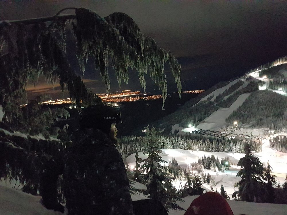 Snowboarder overlooking the local slopes in Vancouver during night time