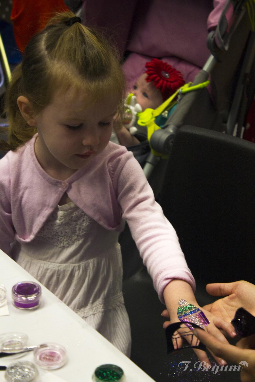 Girl getting glitter tattoo