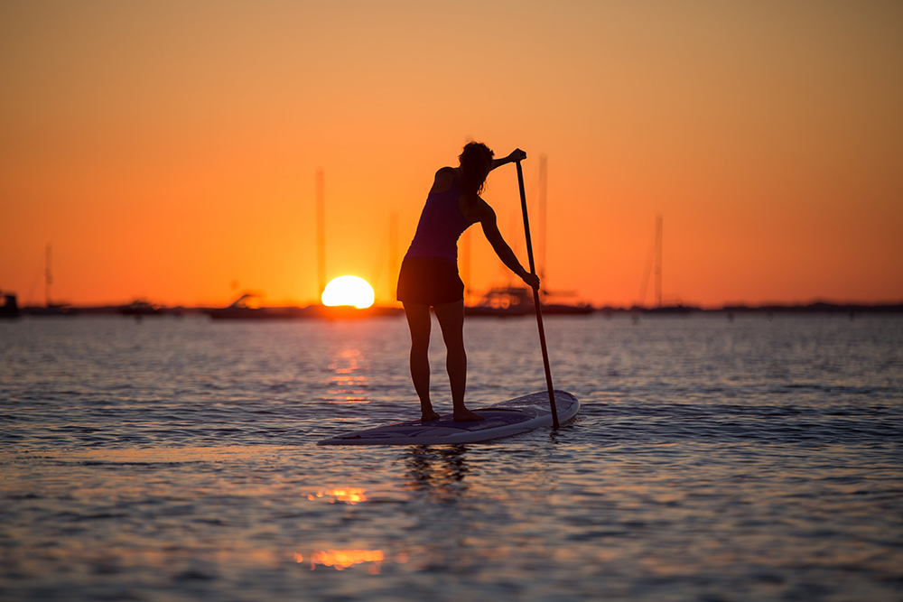 Jamie McGiver of Sup Sackets Harbor wakes with the sun for an early morning paddle on Lake Ontario.  Due West Photography
