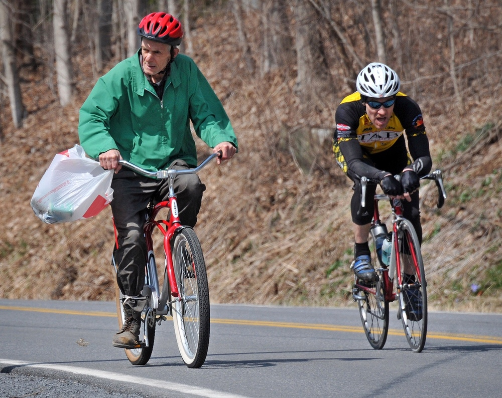 A resident out looking for bottles and cans does his thing on County Rt. 74 just south of Greenwich, seemingly oblivious to the racers flying by him.  2011 - © Dave Kraus
