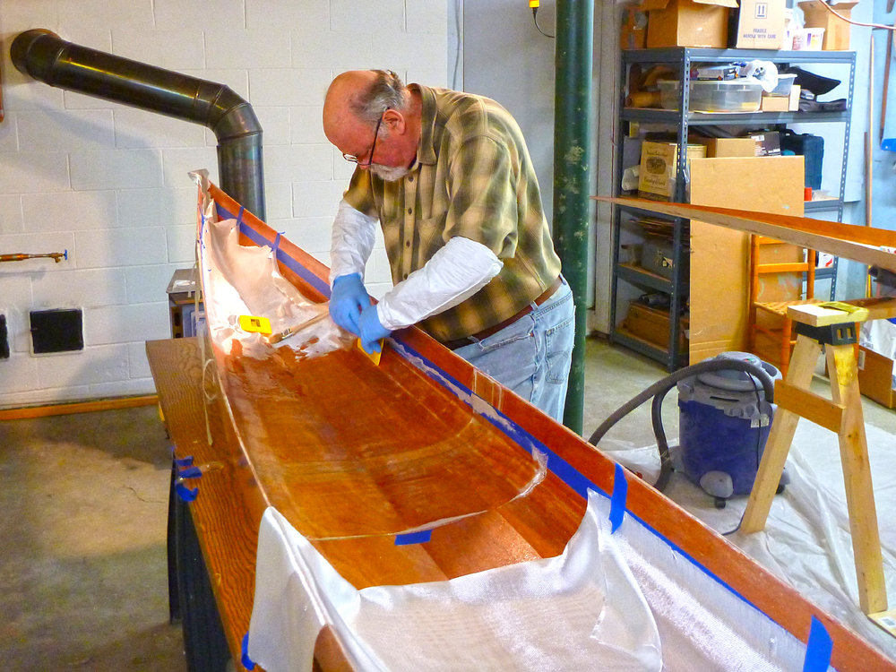 Mike Cavanaugh helps with wetting out the fiberglass with epoxy. Alan Mapes