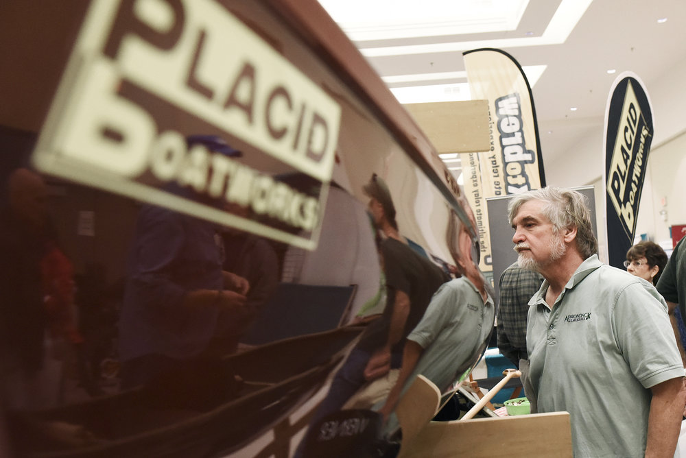 ERICA MILLER / GAZETTE PHOTOGRAPHER  John Ozard, of Albany, looks at a tandem pack boat at Placid Boatworks' booth during the Adirondack Sports Summer Expo at the Saratoga Springs City Center on Saturday afternoon, March 18, 2017.