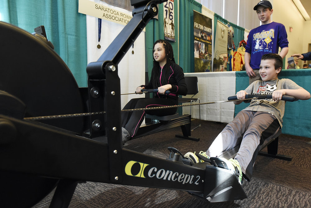 ERICA MILLER / GAZETTE PHOTOGRAPHER  Makayla LaGuerre, 13-years-old of Chestertown, and cousin Carter Coulter, 10-years-old of Queensbury, compete 500m at the Saratoga Rowing Association booth during the Adirondack Sports Summer Expo at the Saratoga Springs City Center on Saturday afternoon, March 18, 2017.