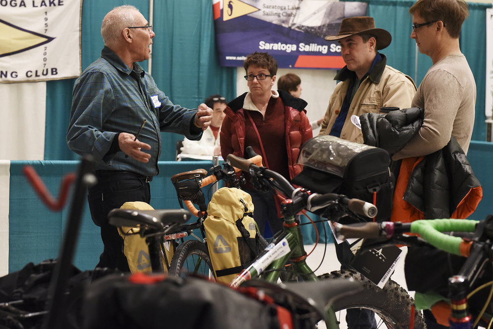 ERICA MILLER / GAZETTE PHOTOGRAPHER  John Blye, of JB invites Exotic Toys, shows (center L-R) Beth Godsil and Rob Hanks of Saratoga, and David Finlayson, of Rexford, bikes at Spa City Bicycle Works booth during the Adirondack Sports Summer Expo at the Saratoga Springs City Center on Saturday afternoon, March 18, 2017.
