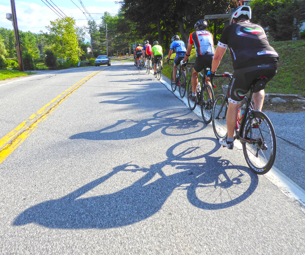Riders on route 8 on the south shore of Brant Lake practice safe single file riding on this busy roadway. Dave Kraus