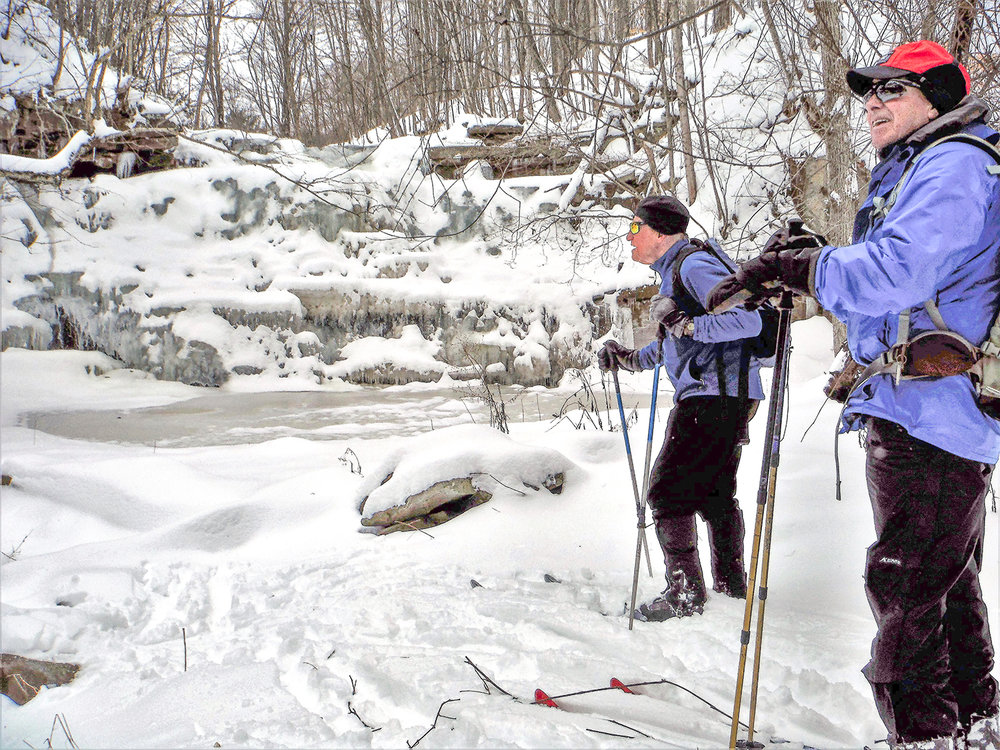 Skiers admire the falls at Wolf Creek Falls Preserve. Rich Macha