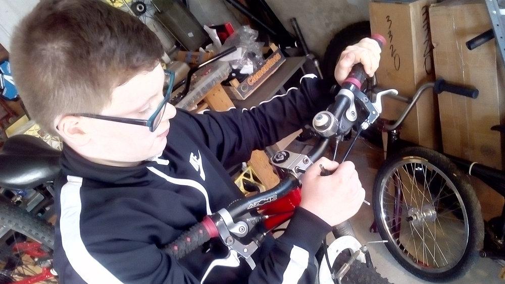 The author's son, Ewan, checks his handlebar bolts, chain ring bolts, and crank arm bolts.  Jim MacNaughton