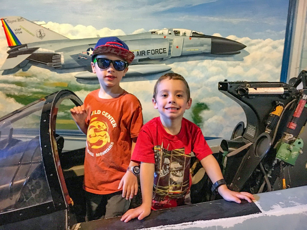 Conor and Theo enjoying the cockpit of a fighter plane.   Tom O'Grady
