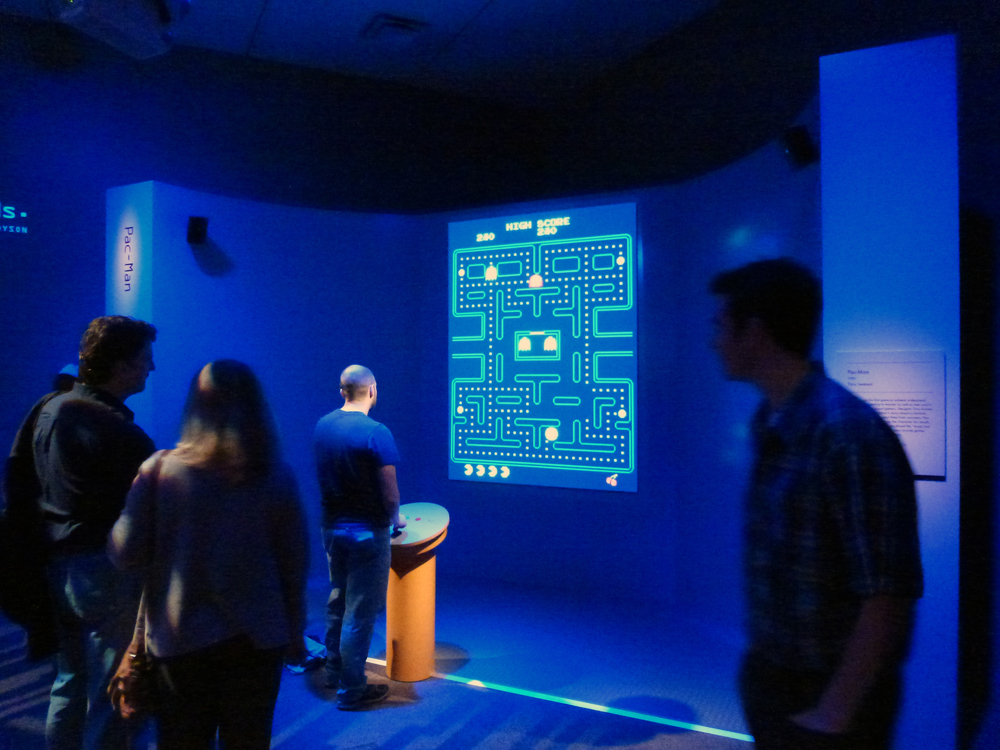 Besides display cases and art, a portion of the exhibit is interactive. Games like Super Mario Brothers, Flower, Myst, Secret of Monkey Island are all playable. Here, a man plays Pac-Man.