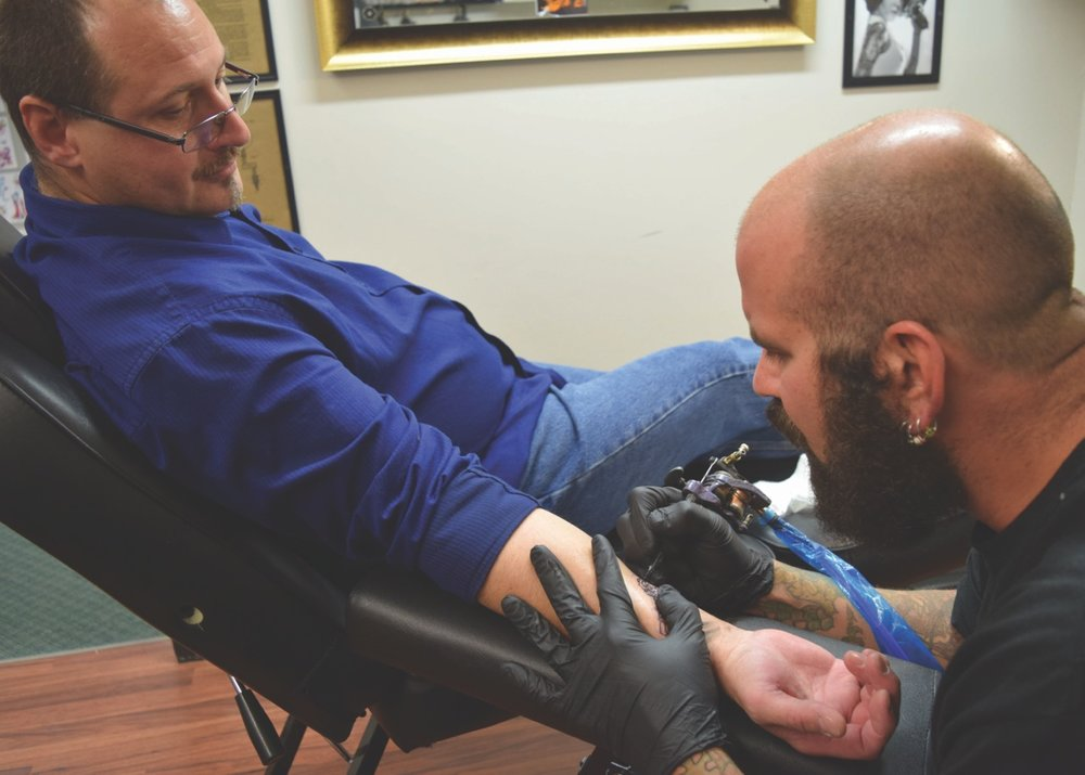 Tattoo artist and co-owner of The Shop Zack Simon, 40, tattoos a key into the arm of Damian Hartzell at The Shop on Dec. 22. The key matches a lock that Hartzell's wife got earlier.