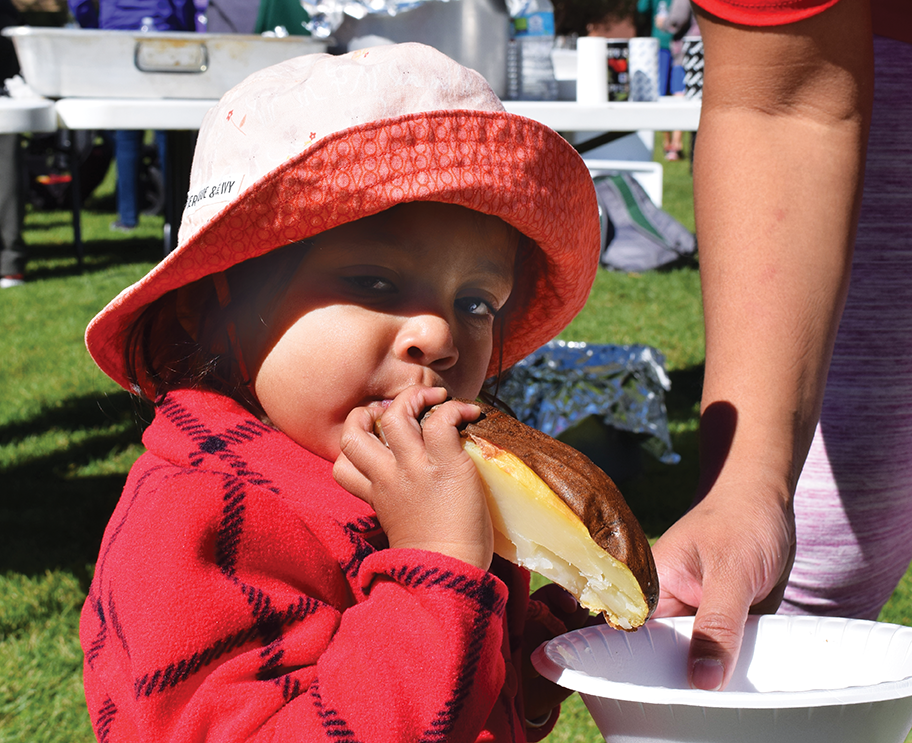 Onaali Pilapitiya, 21 months, chows down on a baked potato at the 13th Annual Stephanie L. Miner 5K Walk and Run on Saturday Sept. 24, 2016. Onalli didn't walk in the race but watched her mom Shalini cross the finish line.