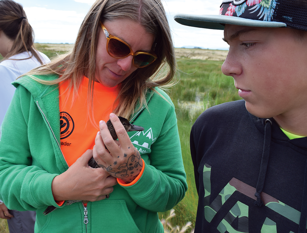 "Stephanie ""Orca"" Ross holds a banded duck as her son Cedar watches at the Monte Vista National Wildlife Refuge on Aug. 8, 2016. Ross was this summer's crew leader of the Youth Conservation Corps."