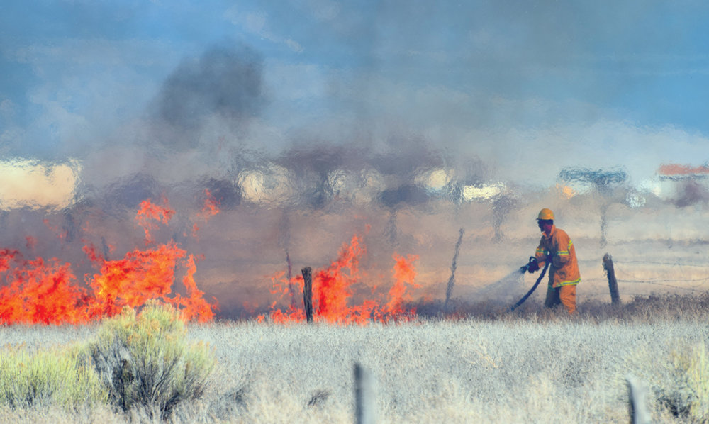 Alamosa firefighter Cody Van Ry sprays water at an uncontrolled brush fire at 3:45 p.m. off of Road Four South on March 13, 2017. No structures or people were harmed. Part of the portfolio that won first place for Class 6 in the Colorado Press Association Better Newspaper Contest in 2018.