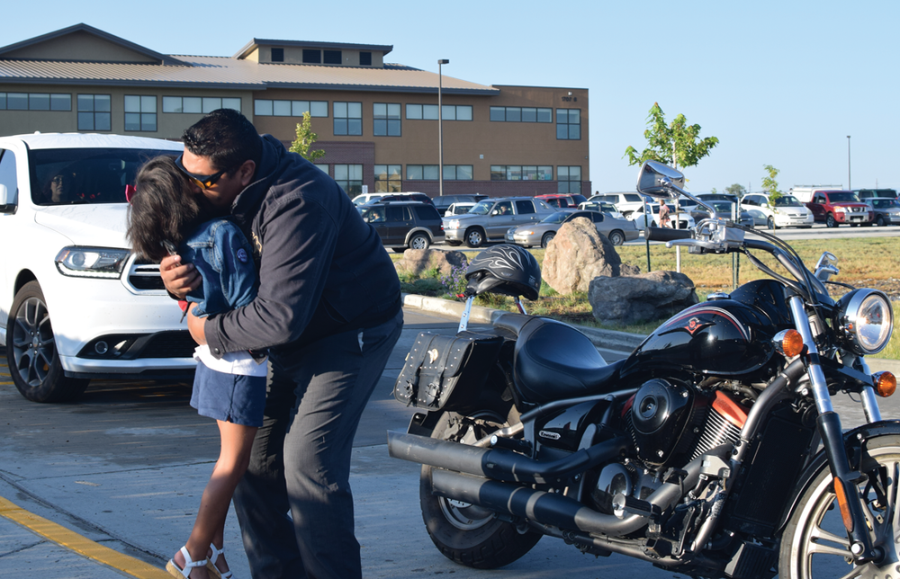 After dismounting from his motorcycle, Mario Linares embraces his daughter Ophelia, 6, as she heads to her first day at Alamosa Elementary School on August 29, 2017. Part of the portfolio that won first place for Class 6 in the Colorado Press Association Better Newspaper Contest in 2018.