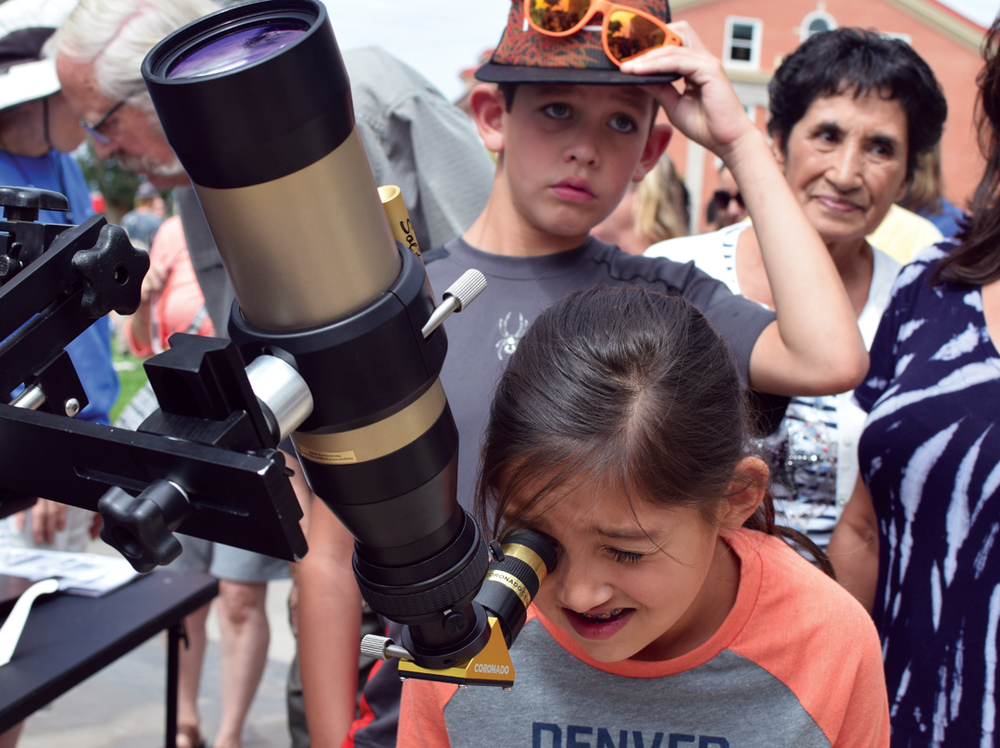 Audrina Mondragon, 8, looks at the solar eclipse through a hydrogen-alpha telescope outside of Adams State University's Zacheis Planetarium on August 21, 2017. The solar telescope gives the sun a crimson appearance .  Won second place for best news photo for Class 6 in the Colorado Press Association Better Newspaper Contest in 2018.