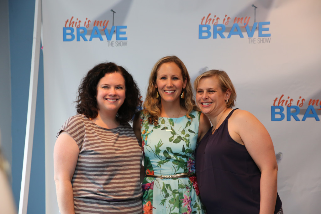 Heather and Hillary pose with Jenn in front of the Brave logo banner.
