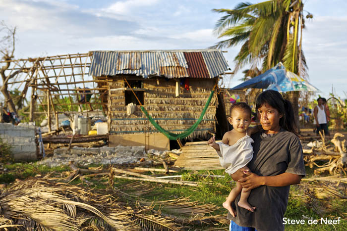 A local Madridejos women and her baby stand in front of her destroyed house after Typhoon Yolanda passed over the island.