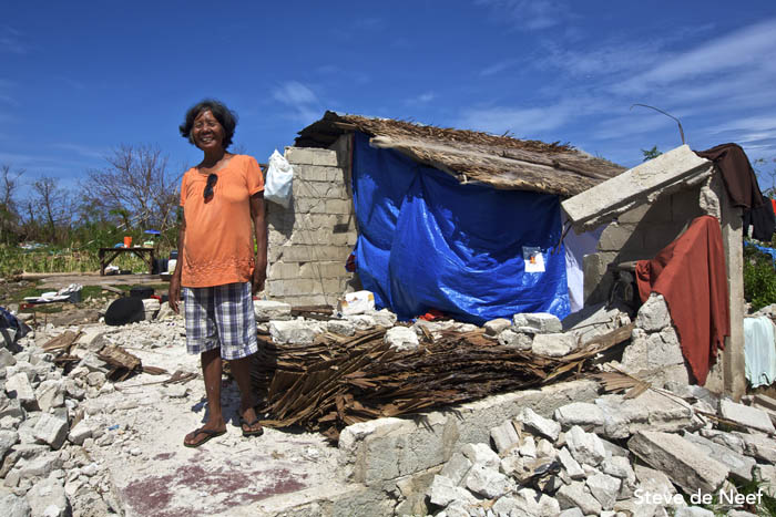 A woman posing in from of her house that was destroyed by Tyhpoon Yolanda.
