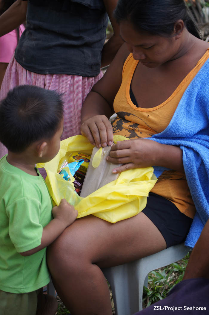 A woman opens one of the packs for her young child. Photo: Chai Apale/Project Seahorse